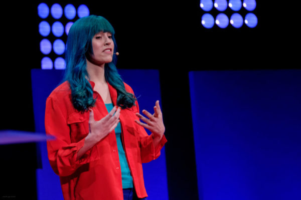 A picture of a green-haired woman giving a TEDx talk on a stage, in front of a large audience